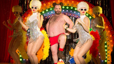 A large bearded man, shirtless, wearing red shorts, bear ears and boots, is flanked by women in silver lame body suits and fur hats. Behind them is a large rainbow with many electric lights.